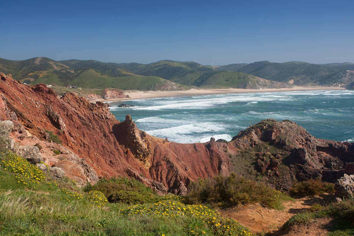 Rota Vicentina Image of ochre cliffs and Praia do Amado beach
