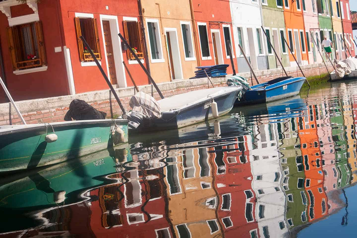 Image of a row of vibrant coloured houses reflected in a canal in Burano Italy