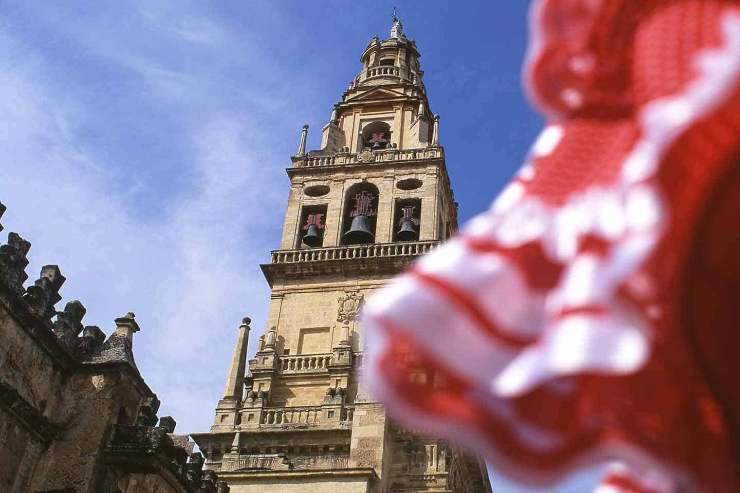 Image of Cordoba flamenco dress with the Cordoba mosque-cathedral belltower in the background