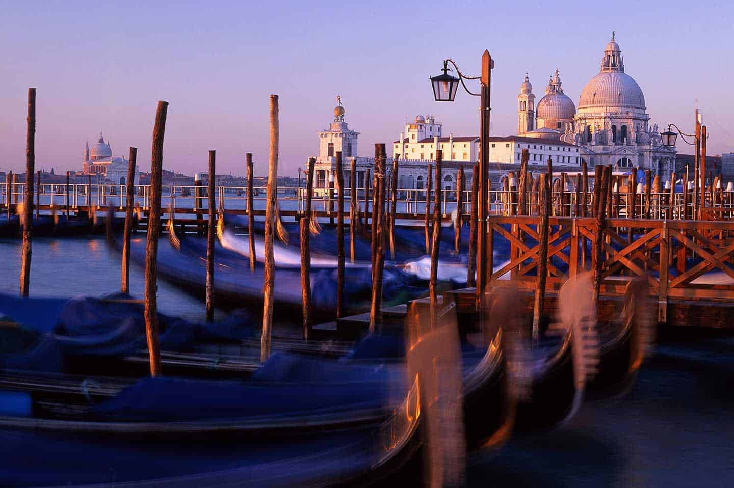 Things to see in Venice Italy Image of Santa MAria della Salute church and gondolas at sunrise