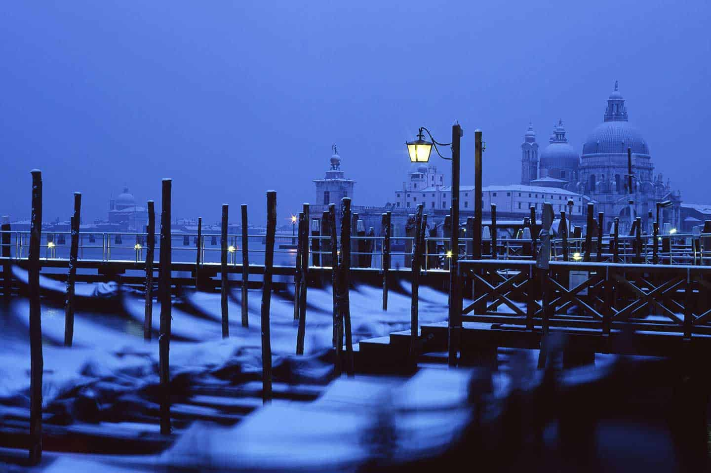 Image of Santa Maria della Salute and gondolas in snow in Venice
