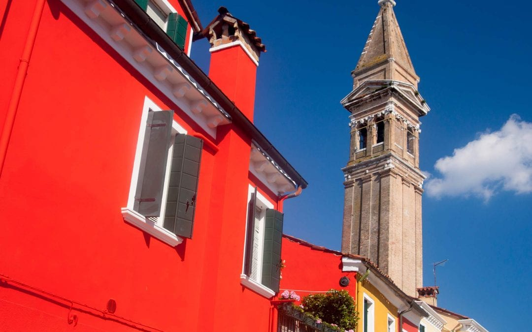 Things to do in Burano Image of bright red house and church tower