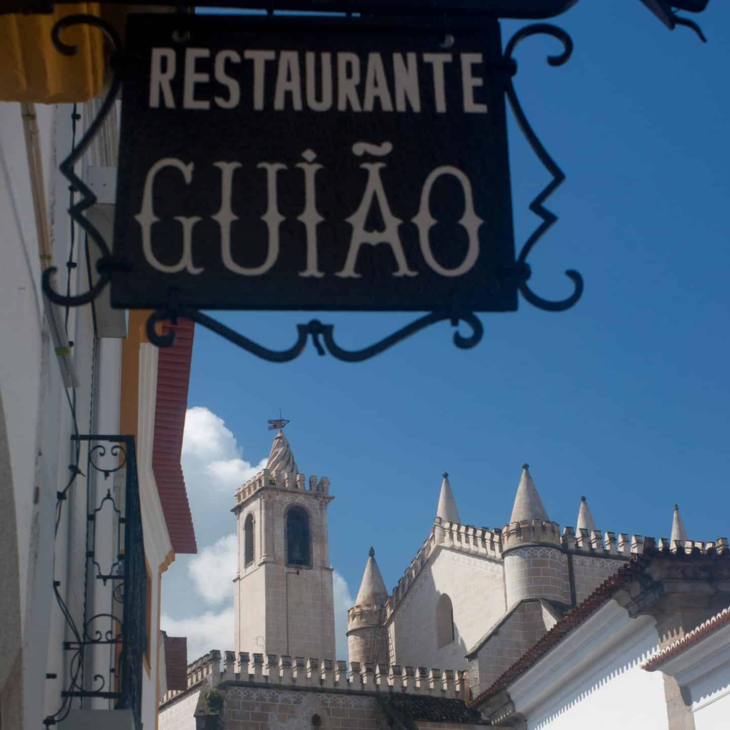 Image of a restaurant sign and church in Evora