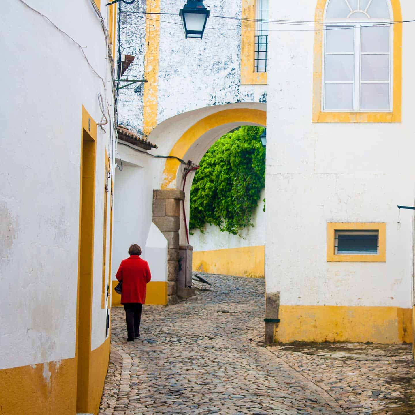 Image of a woman walking through the cobbled streets of Evora's old town