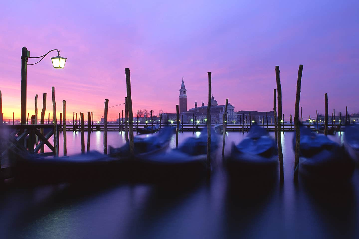 Image of gondolas and San Giorgio Maggiore church in Venice at dawn