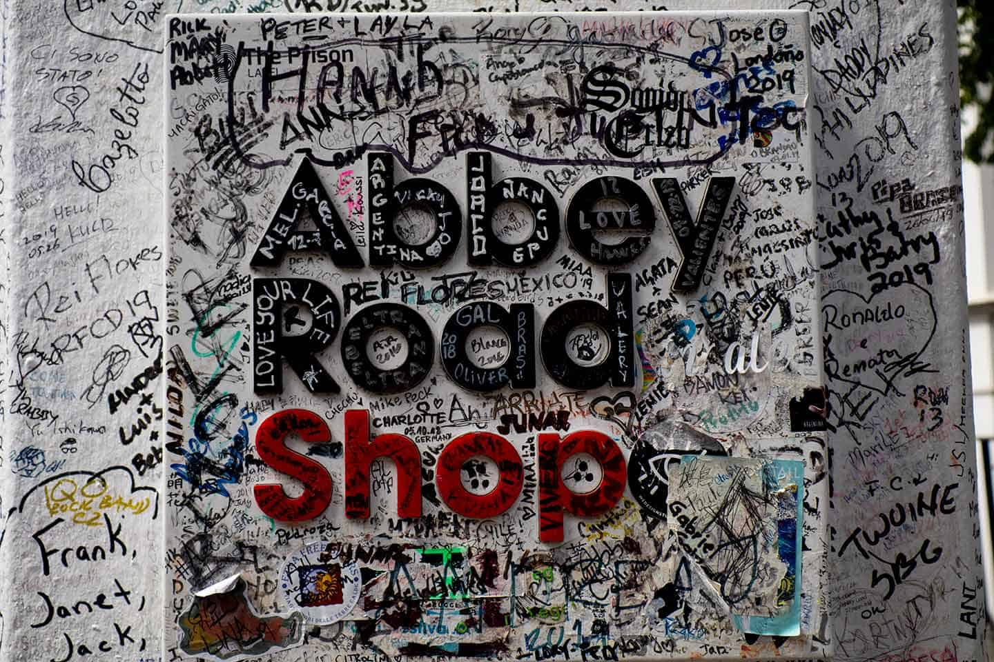 Image of the Abbey Road shop sign in London covered with graffiti
