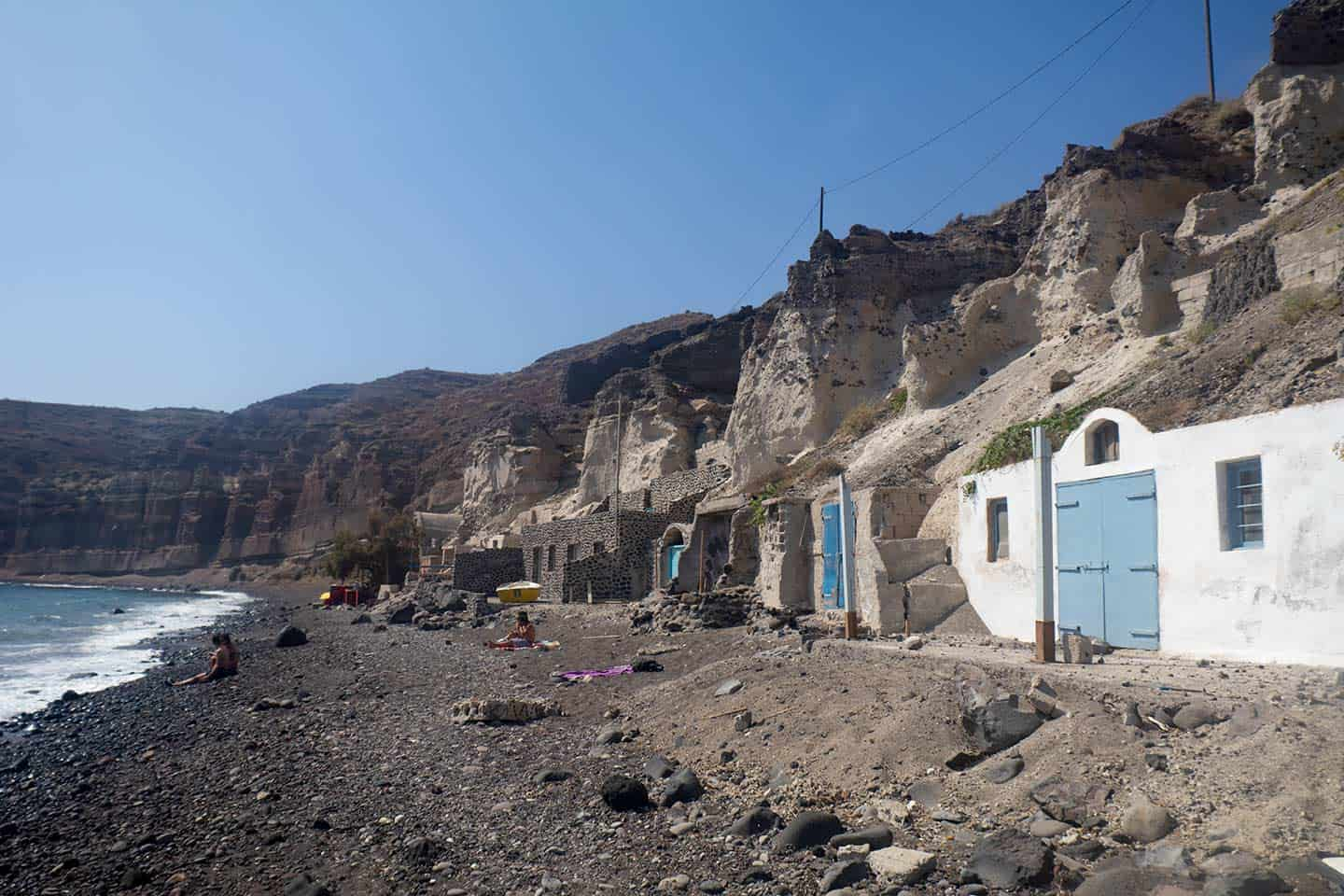 Image of Black Beach in Santorini with houses built into cliffs
