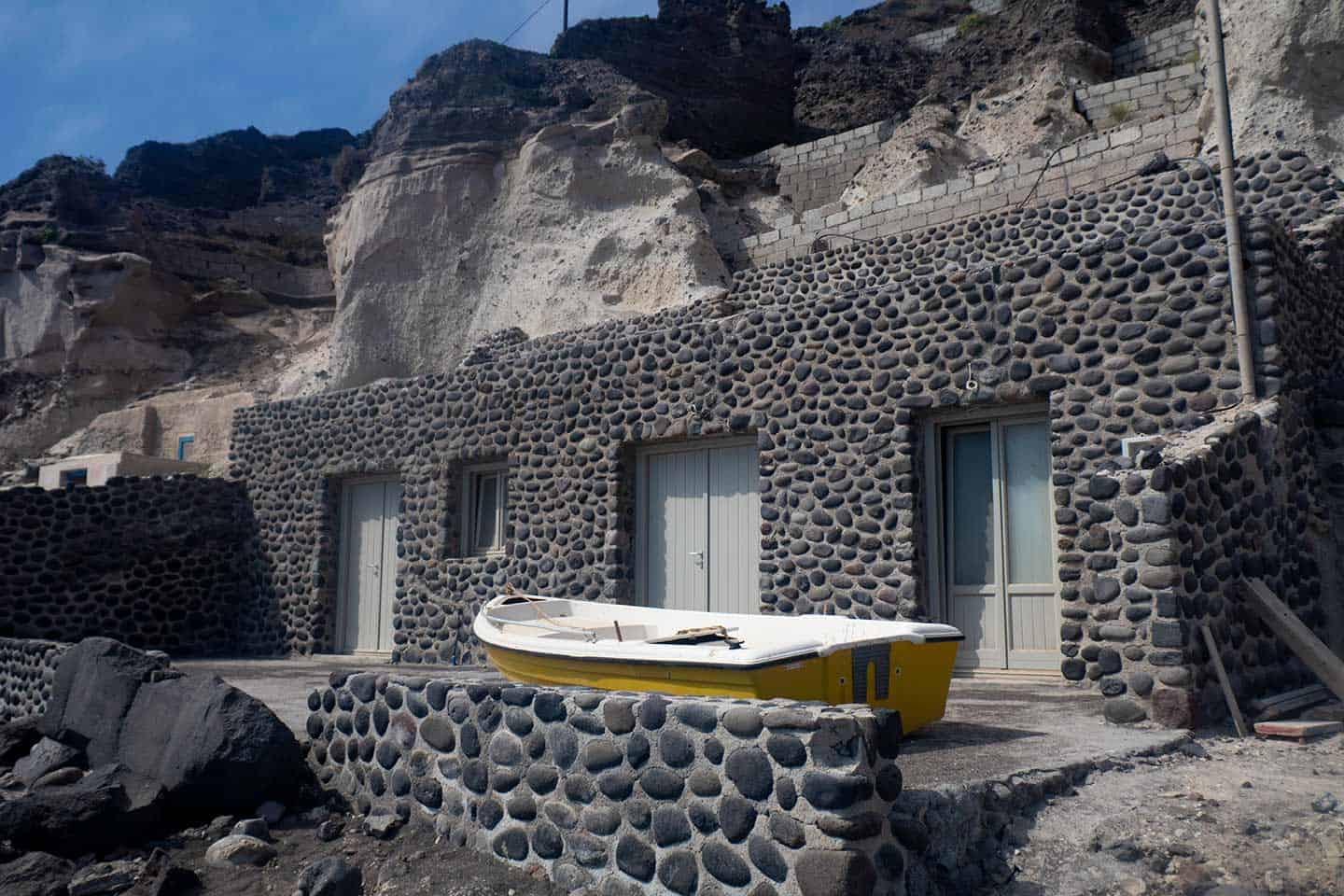 Image of a beach house built into the cliff at Black Beach in Santorini