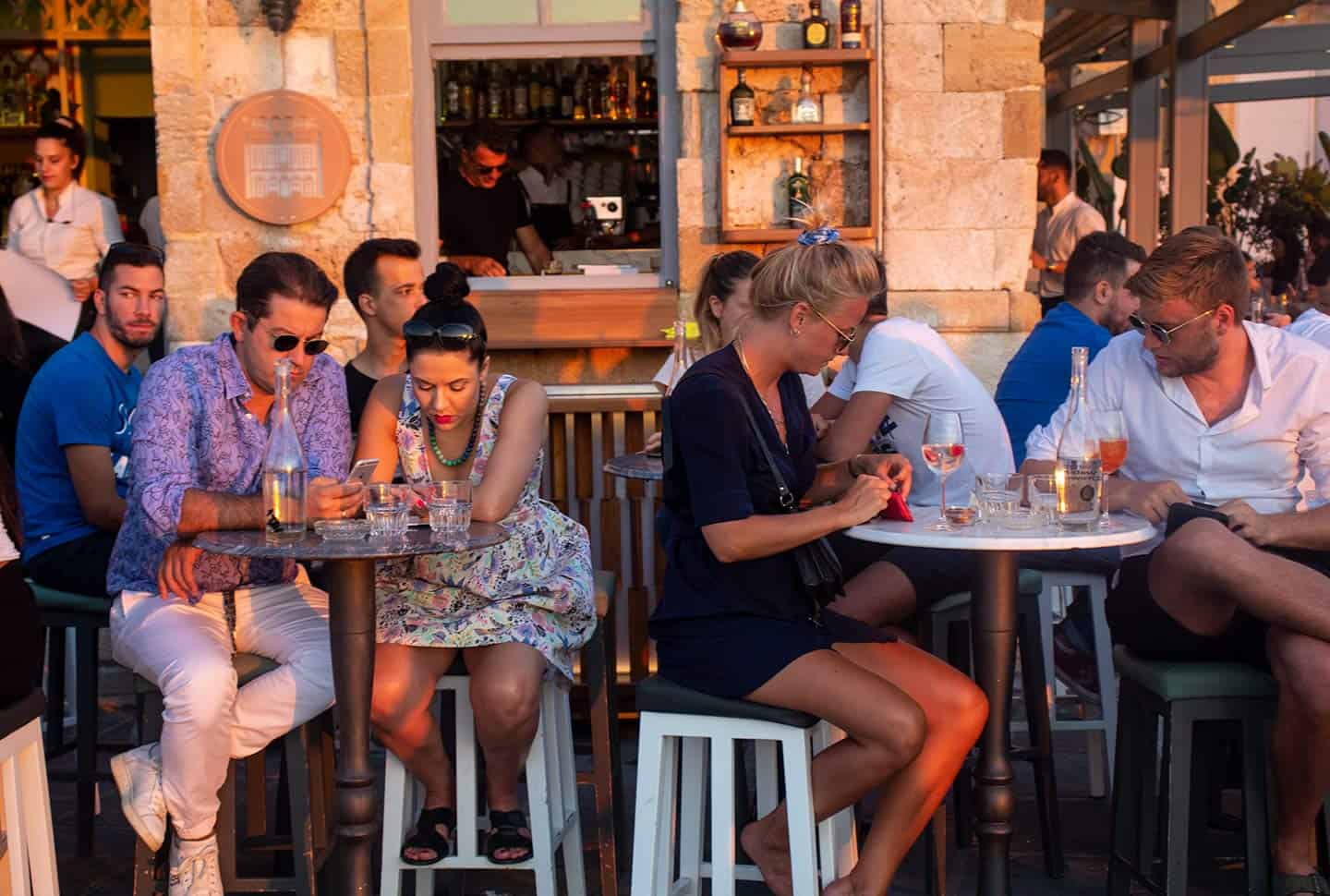 Image of people drinking at bar on Chania harbour