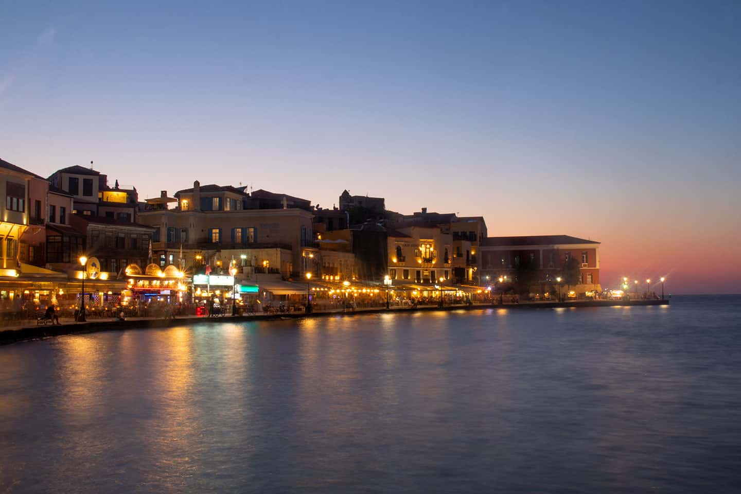 Image of restaurants on Chania harbour at dusk