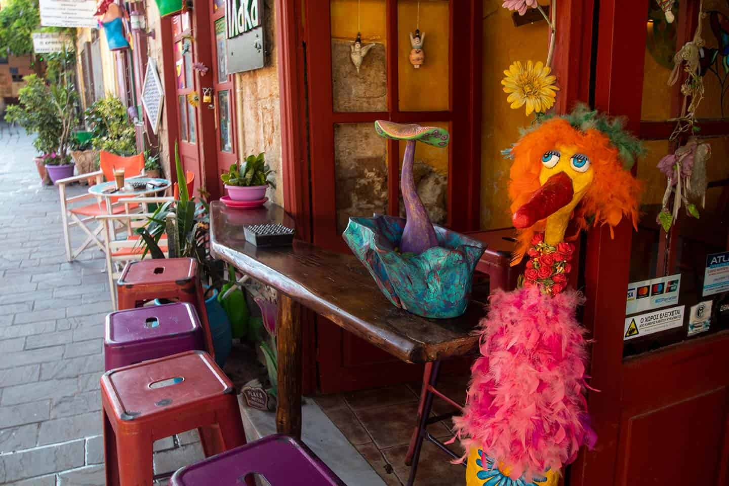 Image of Plaka cafe in Chania with a colourful doll at the entrance