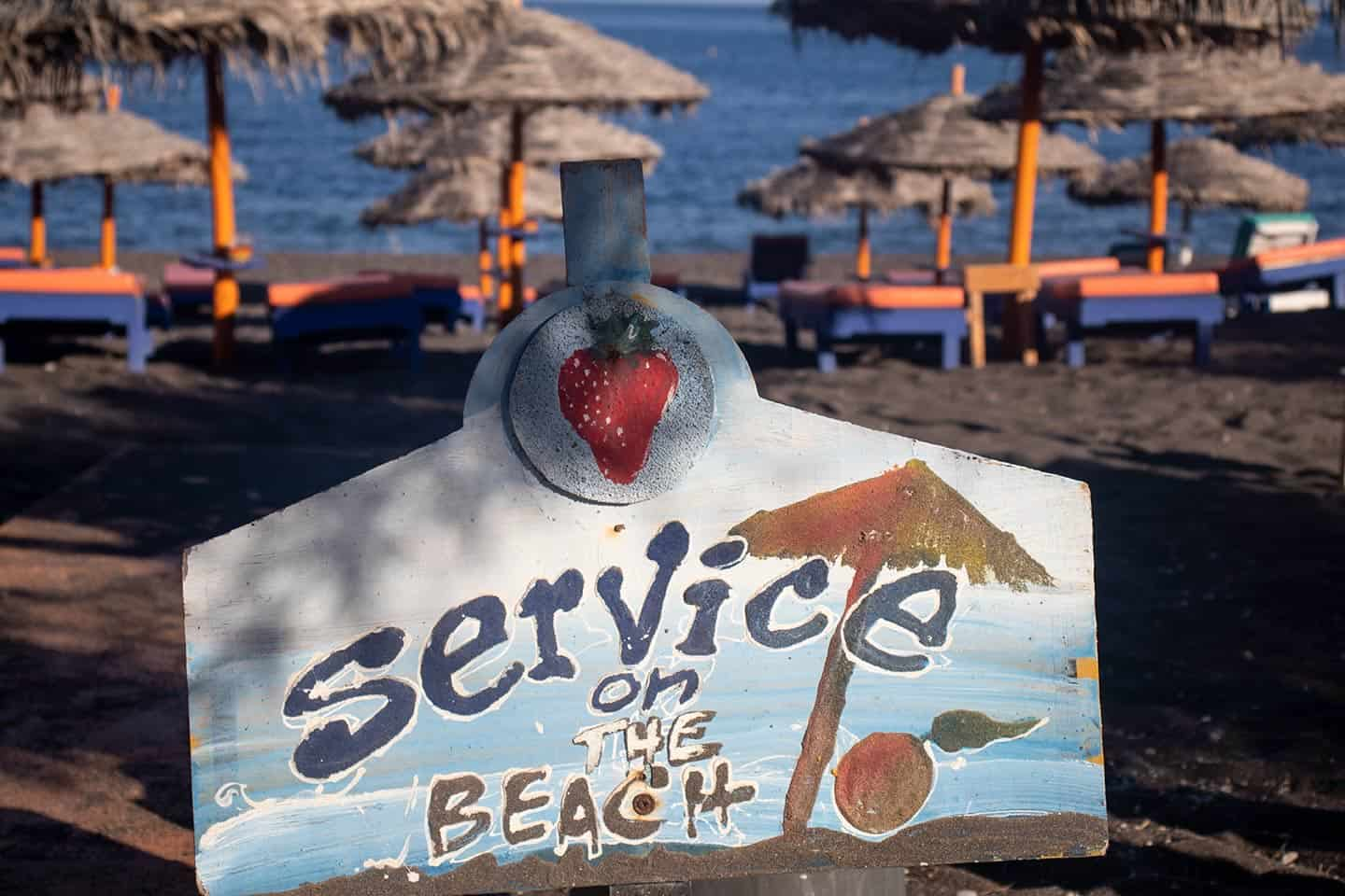 Image of a 'service on the beach' sign at Perissa Santorini Greece