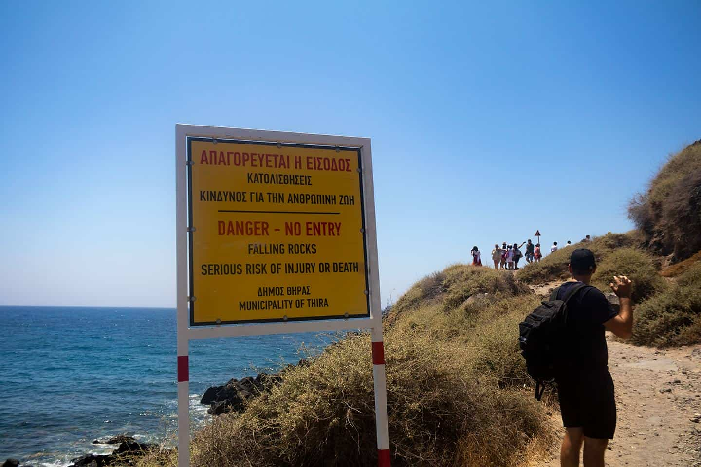 Image of a danger sign warning against visiting Red Beach Santorini
