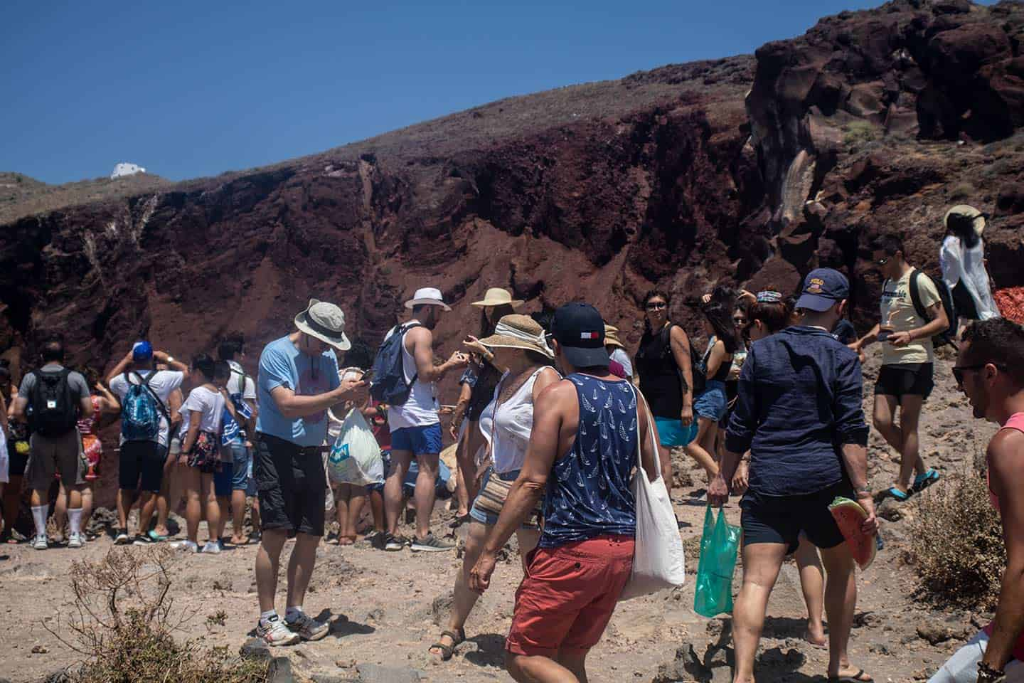 Image of crowds of people at the Red Beach viewpoint in Santorini