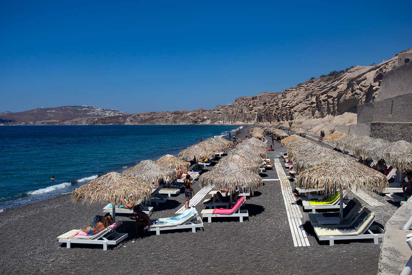 Image of sun shades and loungers on Vlychada beach in Santorini