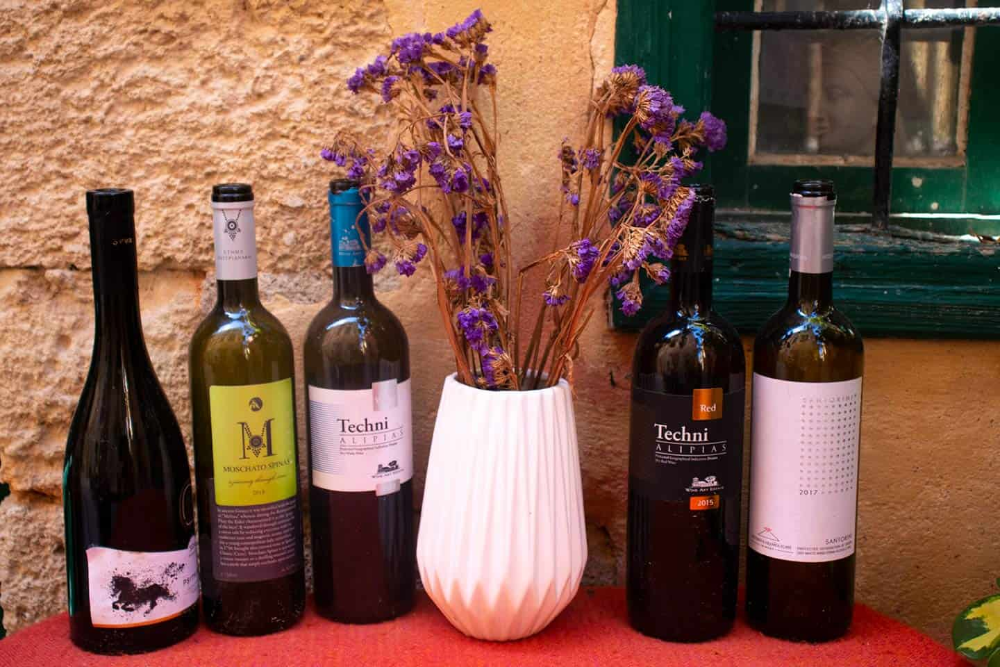 Image of wine bottles and a vase of flowers outside a restaurant in Chania Greece