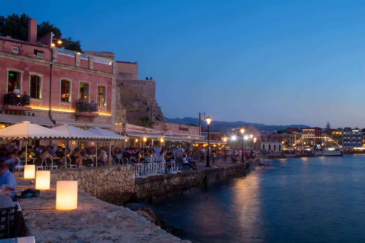 Image of bars and restaurants on Chania harbour at dusk
