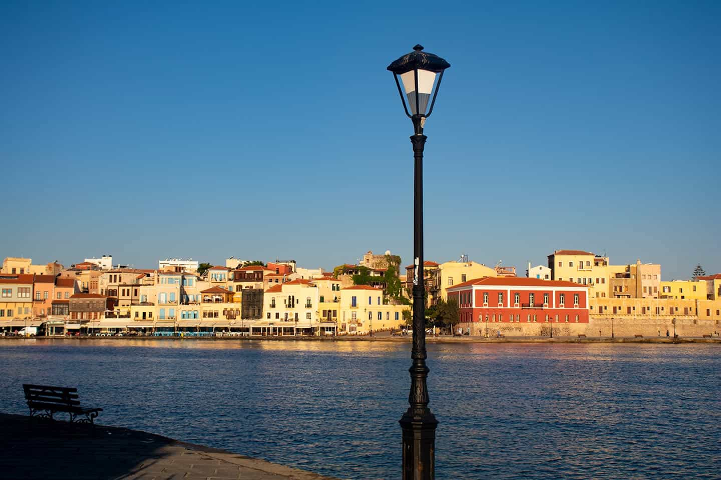 Image of Chania harbour with a lamp in the foreground Crete Greece