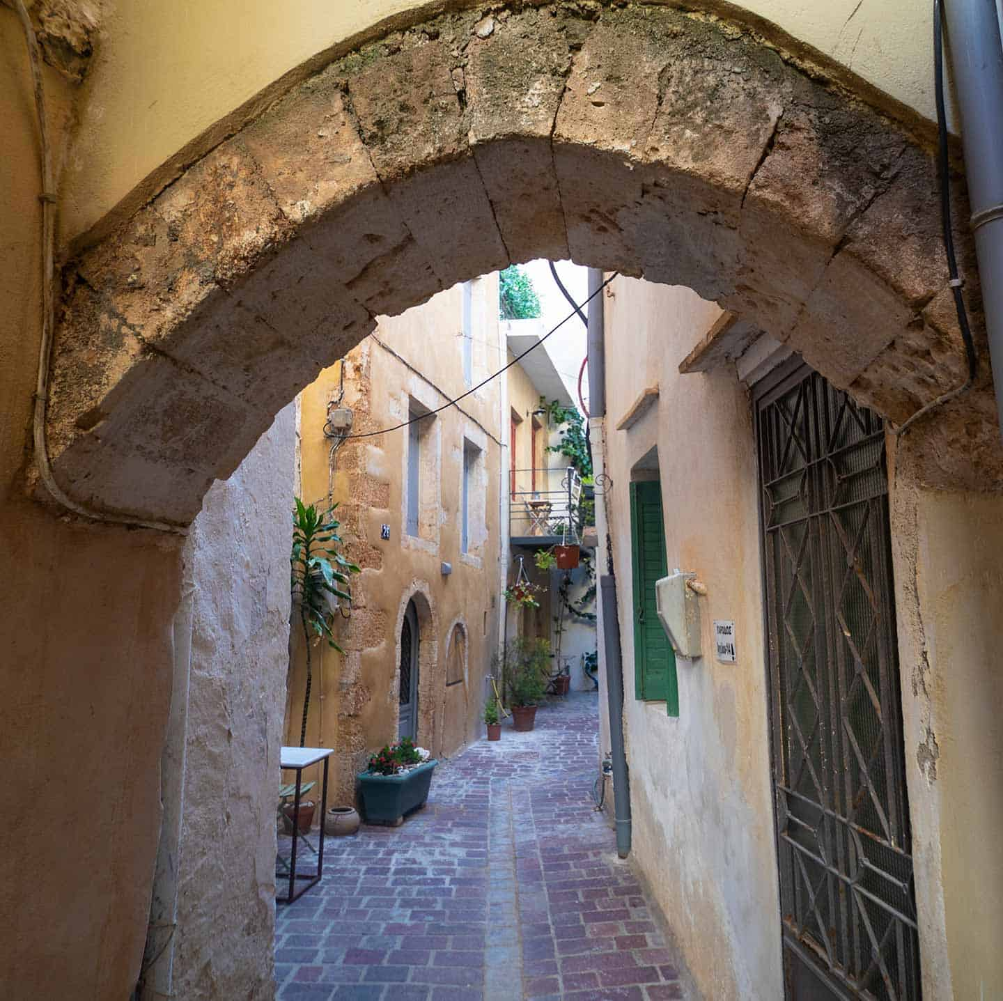 Image of a street in Old Town Chania framed by an archway