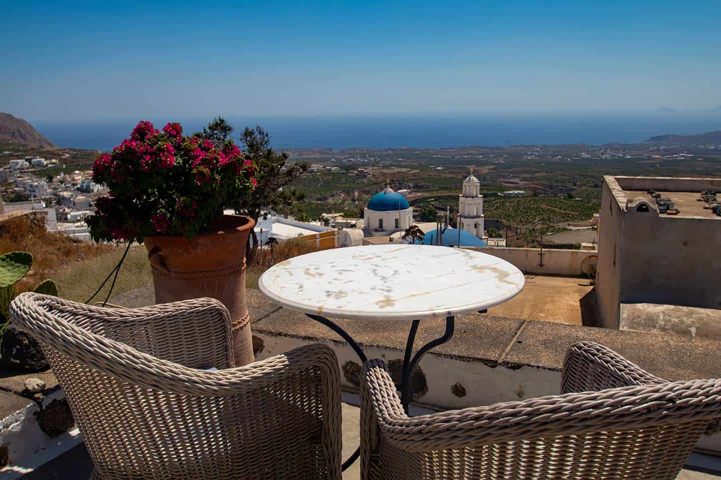 Image of cafe table overlooking Pyrgos and the Santorini coast