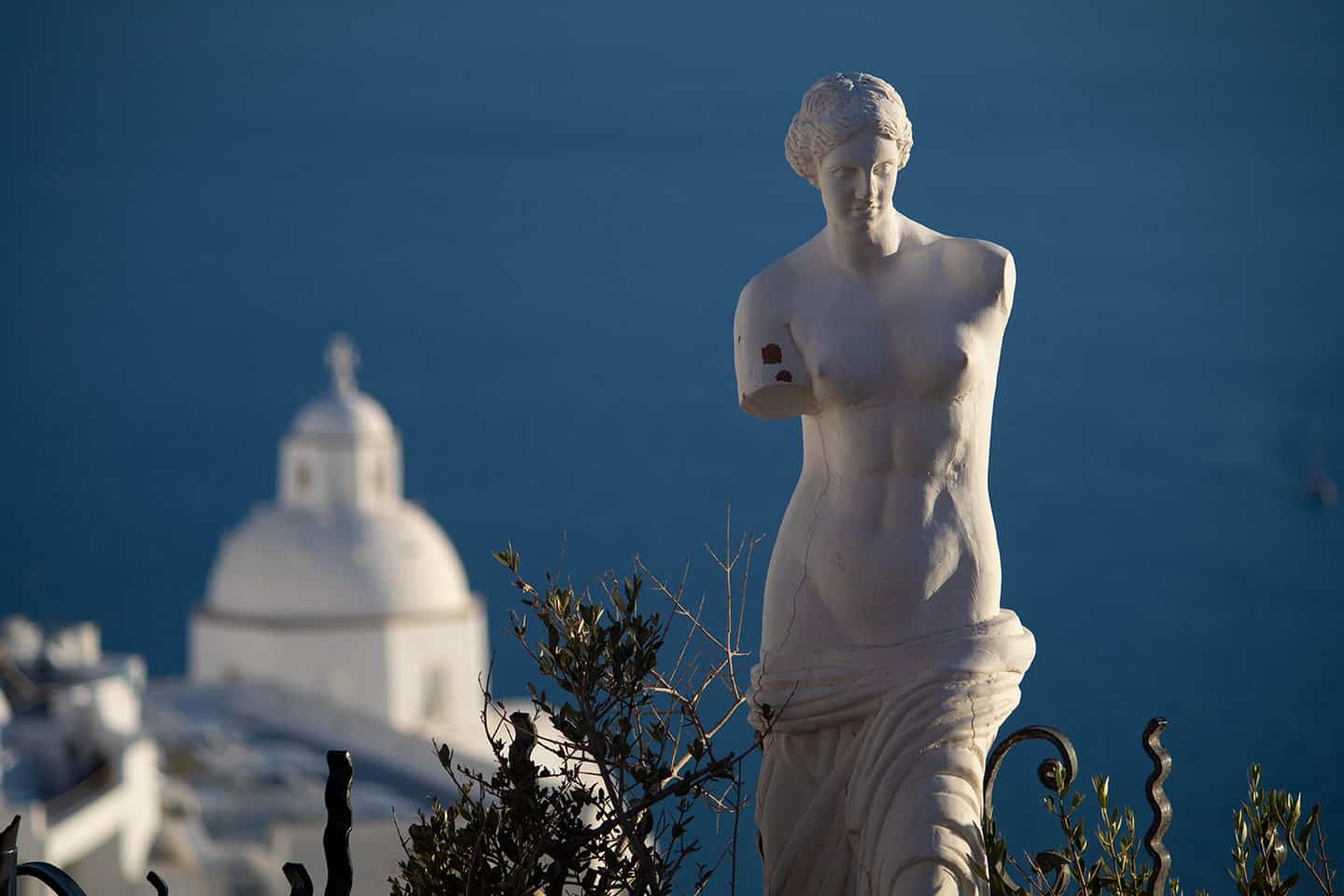 Image of a statue in a cafe in Fira Santorini with a church dome and sea in the background