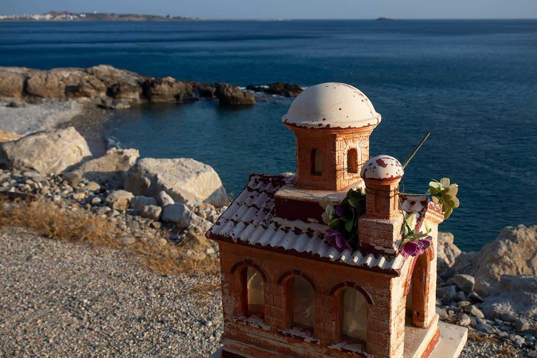 Image of a roadside shrine bove a beach at Paleochora