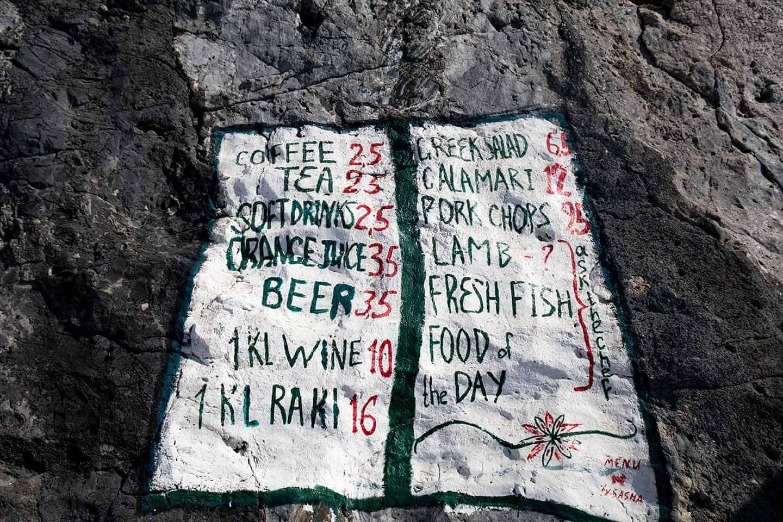 Image of the taverna menu painted on rocks at at Agios Pavlos beach