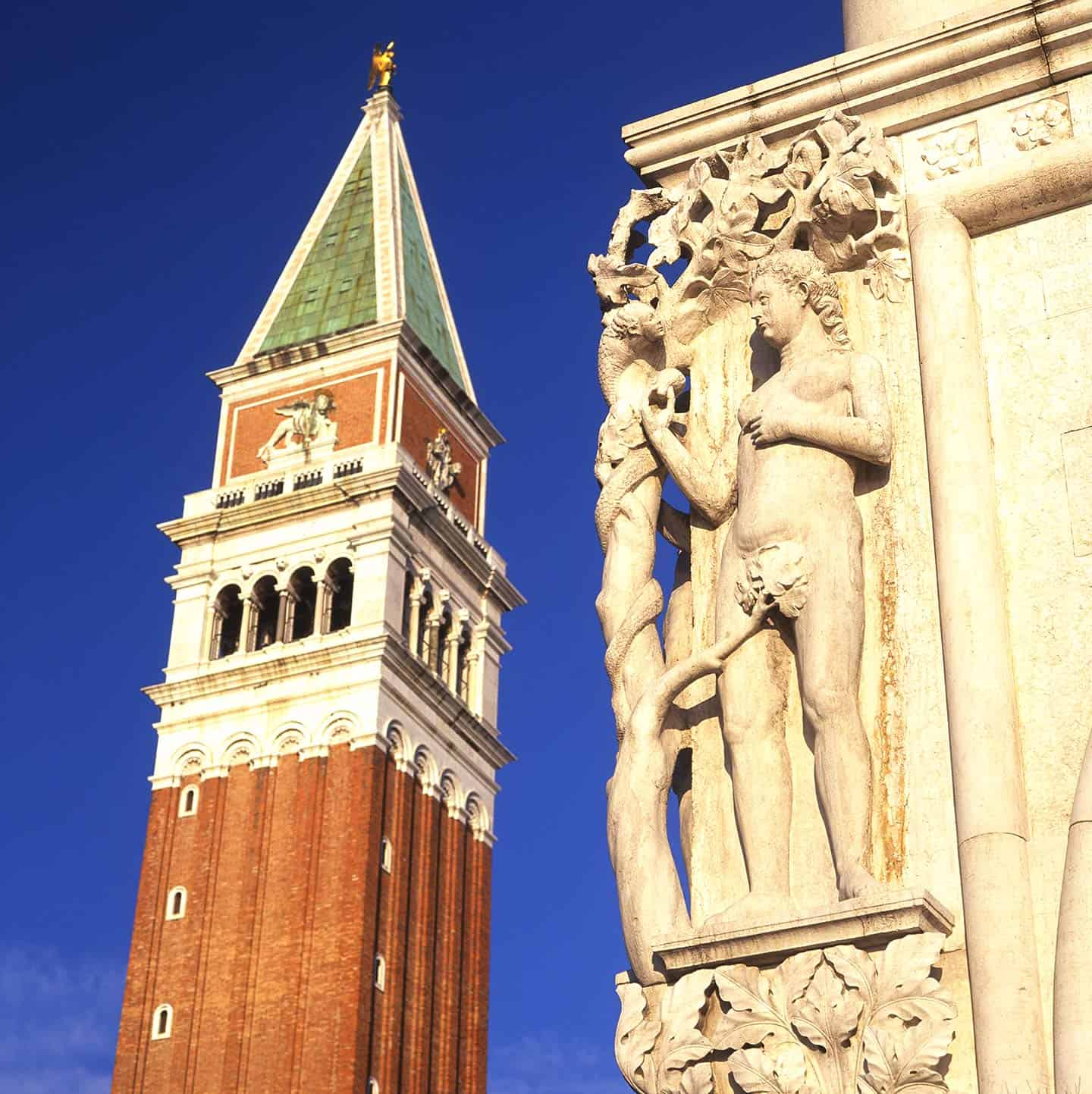 Image of St Mark's Campanile and a statue on the exterior of the Doge's Palace Venice Italy