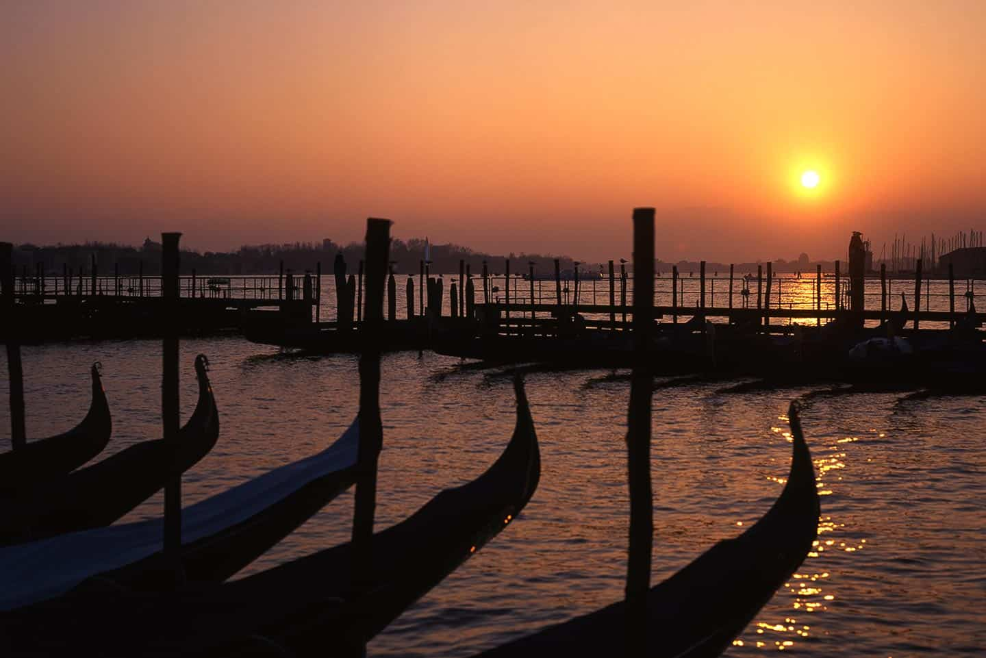 Image of gondolas silhouetted at dawn in Venice